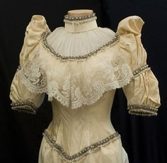 Wedding gown, circa 1883. Made from cream-colored silk faille, the gown is finely embellished with a matching chiffon neckline insert, bands of crystal beads and faux pearls, wide bodice flounce of  handmade Brussels lace, exaggerated puffed sleeve caps and sweeping back train. The gown has the original boned under bodice as well as original silk laces for the back. (front detail)