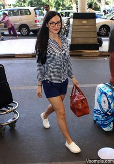 Elli Avram goes geeky chic in blue shorts, checkered shirt, white espadrilles shoes and glasses. via Voompla.com