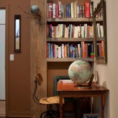 i like the combination of raw wood and earth tones - makes the colorful book spines pop.