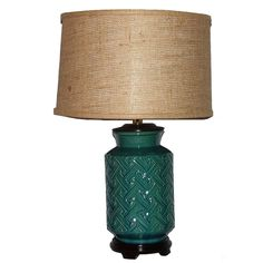 This ceramic table lamp features a teal and dark turquoise distressed crackle finish with an embossed geometric design that will complement many decors. The brown burlap drum shade softens the light and completes the look.