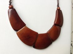 CHUNKY NECKLACE AND DANGLE EARRINGS SET MADE OF ORGANIC TAGUA NUT  This elegant brown jewelry set will be the perfect accesories for this fall season. They are very lightweight, yet very resistant. Its made of Tagua nut, also known as Vegetable Ivory, because of its similarity with actual Ivory.  Tagua nut grows in few countries in South America, our jewelry comes from Ecuador, where local artisans manually carve, dye with Ecofriendly ingredients to create different accesories.  The necklace…