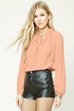 A textured woven blouse featuring a ruffled collar, a split neckline with self-ties and a buttoned placket, long sleeves with elasticized cuffs, and a boxy silhouette.