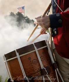 American drummer playing in foreground, in the smokey distance a Continental soldier is on guard next to the American Flag. Shot at Yorktown...