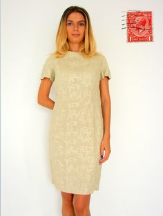 Classy and Sexy Knee Length Cream Dress. The neckline closes with 3 covered buttons opening into a tantalising and sexy open back, which tapers towards the waist, and closes with 4 covered buttons. The cut of this dress is beautiful following the contours of the body, showing just enough femininity. Linen/Cotton type material with fine embroidery.