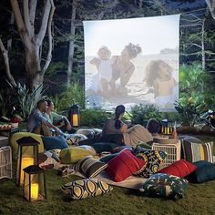 Create your own outdoor movie night. Grab some pillows, some lighting, snacks, a screen and projector