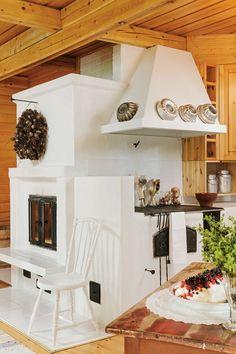 Varaava takka lämmittää talvella koko tuvan. Valkoinen pinnatuoli on äidin isänisän. Leivinuunin reunalla olevat kakkuvuoat ja maitotonkat ovat kirpputorilöytöjä. Punaruskea pöytä on löytö Iisalmen Rompepäiviltä.