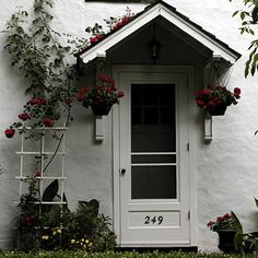 Modest White Entrance Enhanced By Red Flowers. Front Door OverhangRoof ...