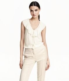 Sleeveless blouse in woven, viscose crêpe fabric. V-neck with ruffle trim and ties at front with decorative tassels at ends.