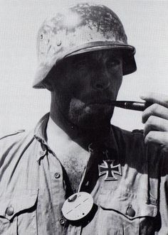 German Afrika Korps veteran enjoying his pipe. Note the casually-worn Knight's Cross and the dog tag as well. North Africa, 1942. Individual identified as the later Lieutenant Colonel Georg Briel (1907-1980). By the time this photo was taken he served as commander of Heeres-Flak-Batallion 606.