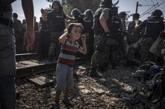 The Year in Pictures 2015 - The New York Times - GREECE-MACEDONIA BORDER, NEAR IDOMENI, GREECE 8/26/2015 A child stood near police controlling a rush of refugees into Macedonia. Sergey Ponomarev for The New York Times