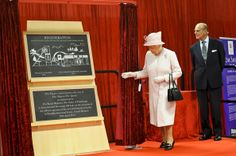 Prince Philip, Duke of Edinburgh looks on as Queen Elizabeth II unveils a plaque during a visit to International Greetings UK Ltd at the Penallta Industrial Estate in Ystrad Mynach during her visit to south west Wales on April 30, 2014