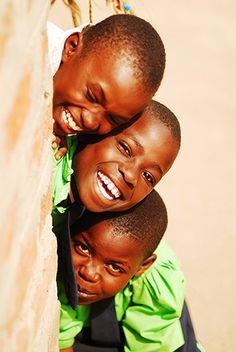 Portrait of 3 schoolboys smiling, Kenya