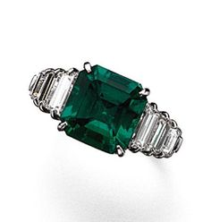 EMERALD AND DIAMOND RING.  The emerald-cut emerald weighing 5.35 carats, flanked by 6 baguette diamonds weighing approximately 2.20 carats, mounted in platinum, size 6, signed Piranesi.