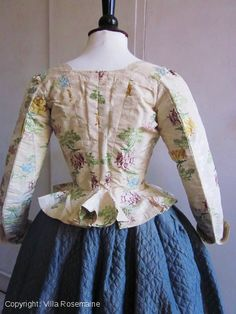 "Back view, caraco with its ""Pet en l'air"", Lyon or Spitalfield, c. 1780-1790. Superb cream damask brocaded with glycines bouquets and pomegranates in gold, purple and blue sky tones. Linen lining corseted front with eyelets for lacing (instead of the rigid bodice!). Pekin silk re-used for the V back and light green chiffon silk for the lining of the sleeves."