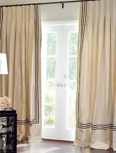 Antique white silk drapery embellished with black striped trim.