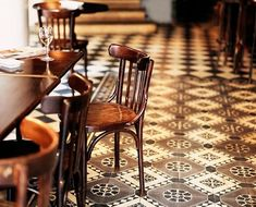 Wooden bistro chairs sit on a Moroccan-inspired tiled floor. Mesa Bonita has been collecting hydraulic tiles for the past 10 years. All the tiles have been saved from the dumpsters and need a second life. They can be turned into a table, console, frame, trivet… Contact me for information, I have a wide selection of styles, colors and a bunch of ideas: Benedicte Bodard Mesa Bonita/Barcelona Tiles benedictebodard@gmail.com www.mesabonita.es https://www.pinterest.com/bbodard/