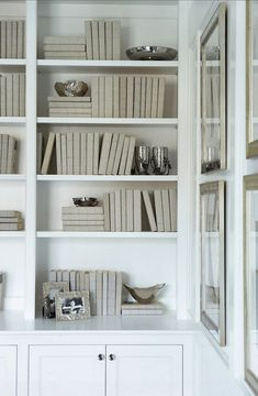 Linda McDougald Design - dens/libraries/offices - Sherwin Williams - Pure White - white built-ins, white bookshelves, built-in bookshelves, built-in shelving, matching books, matching book dust jackets, silver photo frames, silver bowls, silver framed art, , white paint colors, white paint,
