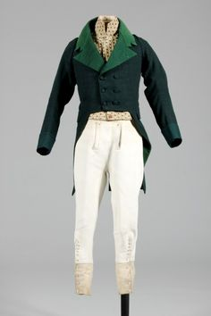 French, early 19th century : green wool hunt coat c.1810-20, with paler green facecloth linings ; soft white leather breeches, c.1800-10, with narrow small-fall and bone buttons, the lower legs with extenders for wearing inside boots, mother of pearl buttons ; the waistcoat of striped 1780s velvet with high stand collar c.1800