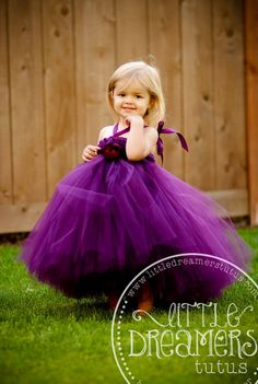 This listing is for our PERFECTLY PLUM TUTU DRESS. Made with tons of tulle in a fabulously elegant shade of plum and featuring ribbon halter straps, adjustable empire waistline with a satin sash that ties in a bow in back. This dress is perfect for weddings, pageants, birthdays and photo ops. *****PLEASE NOTE: The flower shown in the photos in no longer available. A satin sash will be substituted. ****Color Variation between photos is due to lighting and photographer editing. I only have one…