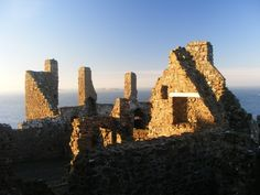 Castles in Northern Ireland - Dunluce Castle as the sun sets. As you can see, the castle is attractively built using thousands of uneven rocks.