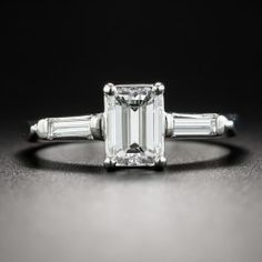 A bright icy-white emerald-cut diamond, weighing 1.02 carats, bearing a GIA Diamond Grading Report stating: F color - VS1 clarity, beams between slender straight baguette diamonds in this sleek classic mid-century engagement ring rendered in gleaming platinum. Understated elegance par excellence. Currently ring size 6.