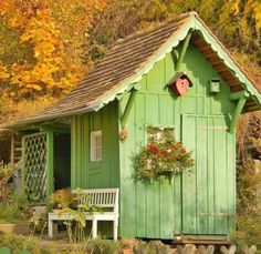 Small Quaint Outdoor Gardening Sheds Quaint green garden shed situated amidst dense trees with a relaxing chair and floral highlightsQuaint green garden shed situated amidst dense trees with a relaxing chair and floral highlights Outdoor Sheds, Outdoor Gardens, Cabana, Shed Decor, Siding Options, Shed Organization, Build Your Own Shed, Simple Shed, She Sheds