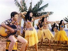 In a scene from the 1964 British film Wonderful Life, pop star Cliff Richard plays the acoustic guitar while accompanied by Hawaiian dancers.