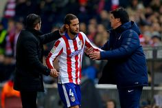 Mario Suarez (2ndL) of Atletico de Madrid is patted on his head by coach Diego Pablo Simeone (L) and his assistant coach German Burgos (R) as he leaves the pitch after being given a red card by referee Gil Manzano during the Copa del Rey Round of 8 second leg match between Club Atletico de Madrid and FC Barcelona at Vicente Calderon Stadium on January 28, 2015 in Madrid, Spain.