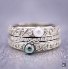 We can't get enough of this gorgeous vintage-inspired pearl engagement ring set! This piece turns lots of typical engagement ring concepts upside down making this set truly unique! The rare choice of pearl gets things rolling in a non-traditional direction, and then we opted to pair a white Akoya pearl and a black Tahitian pearl, making two bands with an eternity band nestled in between. Beautiful accented with milgrain scrollwork. An instant classic!