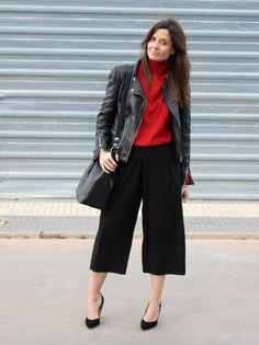Blogger de moda con pantalón culotte negro, cazadora de cuero, jersey rojo.