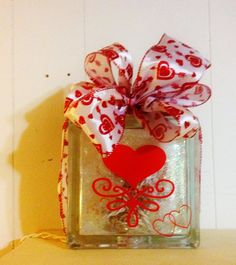 Need a gift for Valentines Day? Forget the candy & flowers! This beautiful Love Glass Block will make the perfect gift or decoration for Valentines Day, Wedding, Anniversary or any special occasion.  It is a double sided & comes in your choice of either 5.5 x 5.5 x 3 or 8 x8 x 3block (choose from drop down). One side has Love inside a silhouette vinyl heart & the other side has a solid red vinyl heart with swirl scroll design. Double silhouette mini hearts are on the bottom corner...