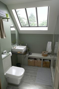 This loft converted bathroom has created a handy seating step that sits in the area where the roof slopes down. Great use of space!