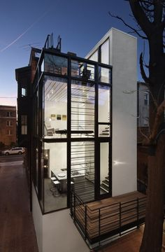 Barcode House, by architect David Jameson, is a free-standing glass and steel extension of a traditional Washington, D.C., row house. The relatively narrow site footprint resulted in a vertically focused two-story structure that's airy and near-transparent. The house includes an outdoor balcony, as well as a large roof deck. Bedrooms are located in the white rectangular structure to the right.
