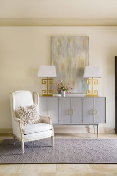 Chic space with gold lamps, smeared painting, fresh tulips, white chair, ruffled pillow, purple rug   Katie Grace