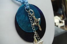 This is a lovely necklace homemade by me. It is made with 2 different color blue thin sliced shell disk with charms of a cross, dove, small cherub