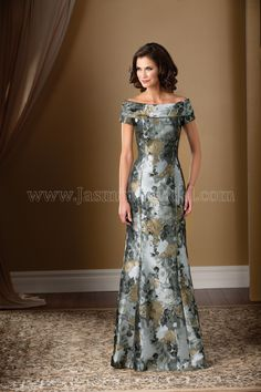 Jasmine Bridal Mother of the Bride/Groom Dress Jade Couture Style K178016 in Gold Couture Floral Jacquard Pattern. This gorgeous gold and grey flower patterned gown will sweep you off your feet! Feel glamorous and sophisticated with this floral jacquard special occasion gown. The boat neckline of this dress is accentuated with a draped cowl detail at the neckline, and when combined with the classic A-line skirt, the dress gives off a feeling of timeless elegance.