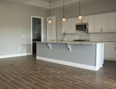 Wood-look tile can help you achieve an open floor plan with continuous flooring. The durability of tile makes this flooring selection a no-brainer! 🏠: Sollevare Homes 📸: Addie Sage Photography . Ceramic Floor Tiles, Tile Floor, Black Splash, Wood Look Tile, Porcelain Ceramics, Open Floor, Countertops, Sage, Kitchen Design