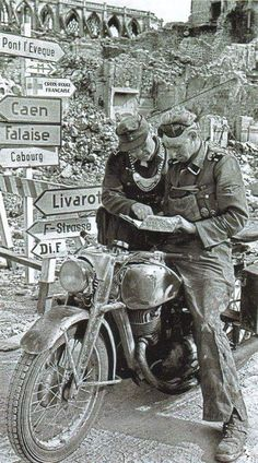 A motorcycle courier gets road directions from a traffic coordinator wearing the large neck worn insignia medallion.