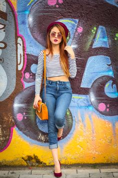 burgundy fedora & pumps, striped crop, rose gold shades, tangelo purse, cuffed blue denims, waistlength straight strawblonde hair