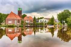 Netherlands, beautiful reflections of a church and houses along the waterways in Holland