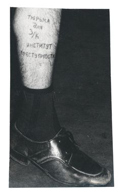 Text on the leg reads 'Prison for a zek is a university of crime'. This tattoo means that an ordinary person who is sentenced for a minor offence will inevitably improve his criminal skills in prison, as professional criminals share their experience.
