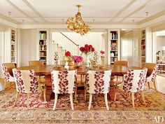 A Lindsey Adelman Studio chandelier hangs above the dining room's table and suite of Jonas chairs | archdigest.com
