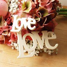 Weißer Schriftzug LOVE aus Holz als Brautstraußanhänger oder Tischdeko zur Hochzeit.