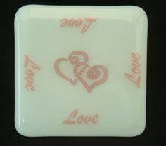Glass coasters of transparent glass with a white base panel and a pink decal in the LOVE theme series. Size approx 10cm x 10cm