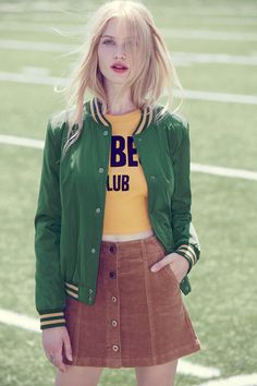 A woven varsity jacket featuring striped trim, a button front, two front button slit pockets, quilted lining, round neckline, and long sleeves.
