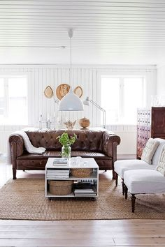 Swedish farmhouse living room with leather chesterfield, white slipper chairs, white paneled walls, modern light pendant, sisal rug THE COFFE TABLE