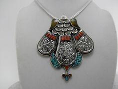Collar etnico artesanal tibetano hecho de turquesas, coral y ambar.  Mide 8 cm. de alto y 7 cm. en su parte mas ancha.