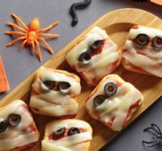 Make funny mummies by baking little pizza's wrapped in string cheese strips in the Pampered Chef Brownie Pan #halloweenrecipe #halloweenparty