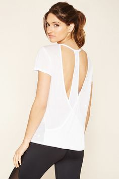 An athletic top crafted from semi-sheer burnout knit featuring a surplice cutout T-back with a mesh insert, a round neckline, and short sleeves.