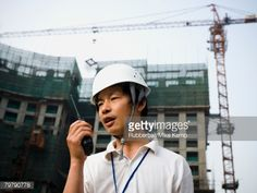 Stock Photo : Man with construction helmet and crane in background holding walkie talkie